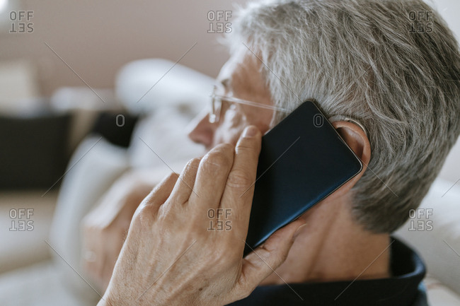 Senior man with hearing aid on cell phone