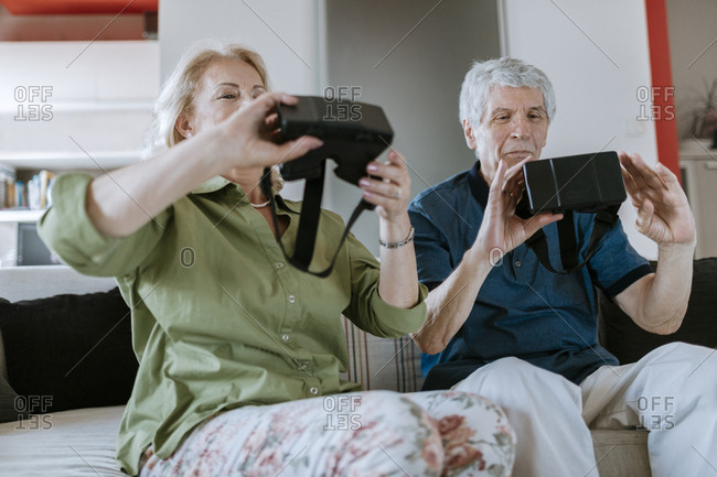 Senior couple at home sitting on couch holding VR glasses