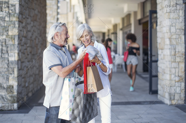 Senior couple taking a city break- going on a shopping spree