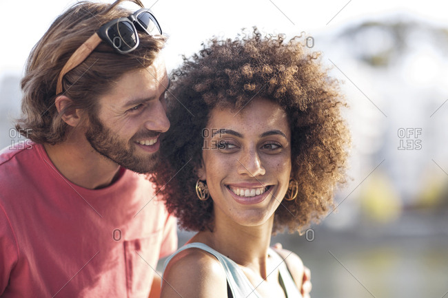 Happy young couple- man whispering into woman\'s ear