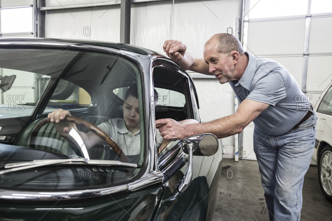 A caucasian senior male car mechanic shows his grandson the driver's view from the driving seat of an old car in a classic car repair shop.