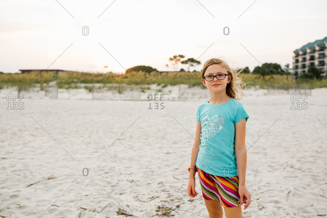 Blonde girl wearing glasses standing on sandy beach