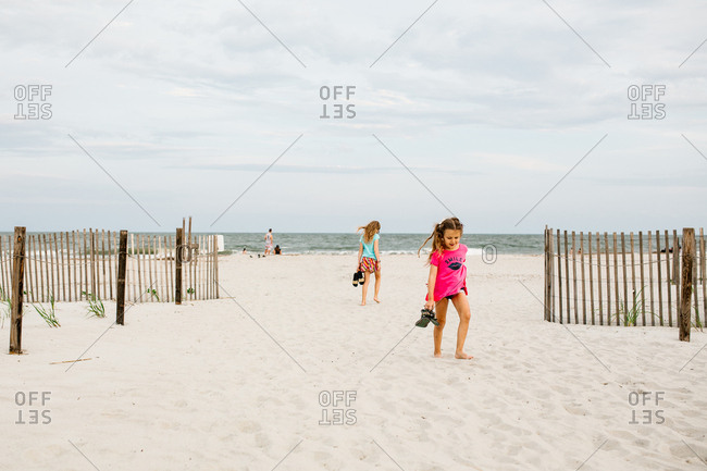 Girls holding their sandals while walking barefoot on a sandy beach