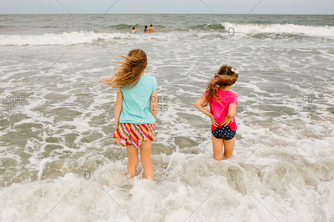 Sisters wading in the ocean waves together