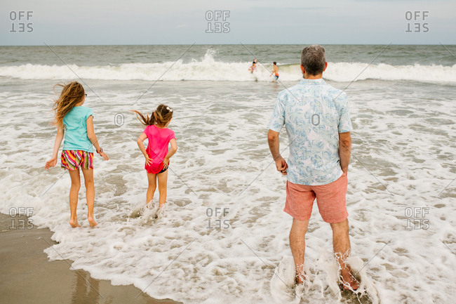 Father and his two daughters wading together in the ocean