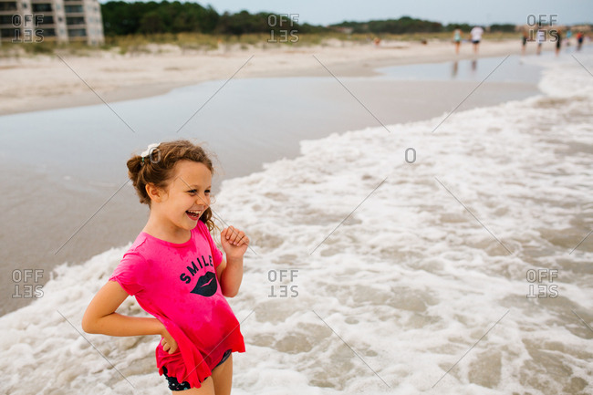Laughing girl wading in ocean waves on the beach