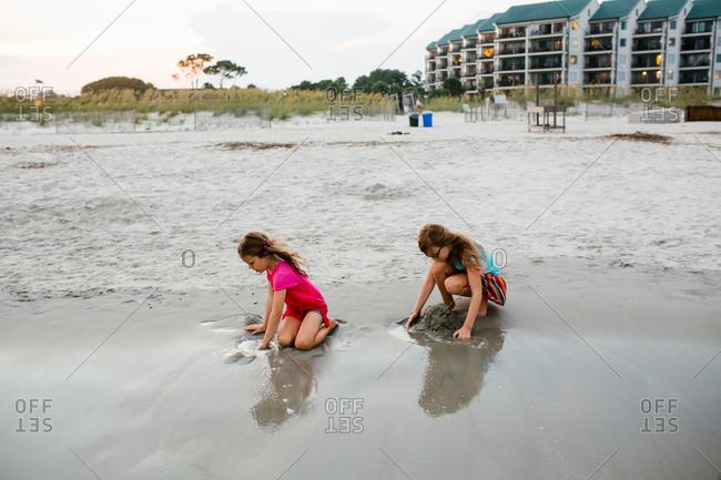 Sisters building sandcastles in wet sand together