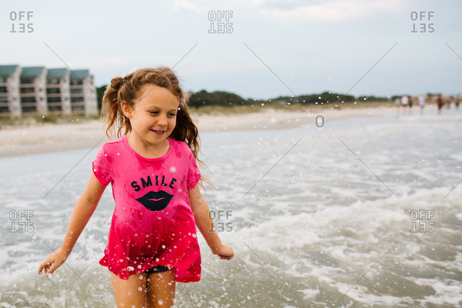 Smiling girl wading in ocean waves on the beach