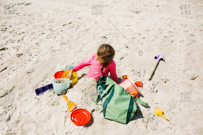 Girl buried in sand surrounded by beach toys