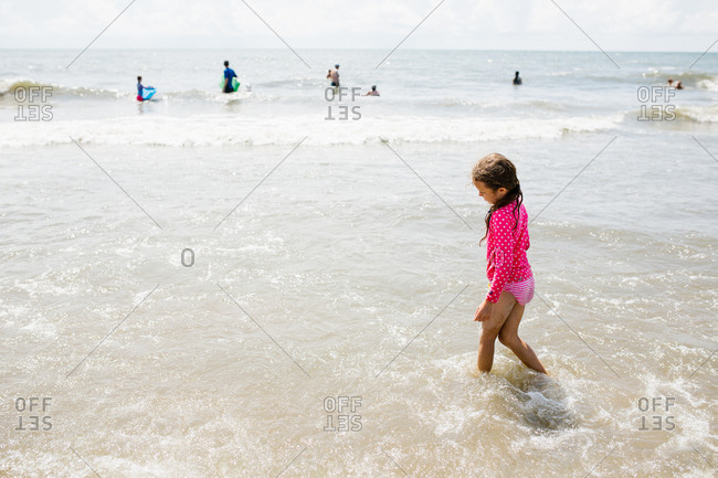 Girl wading through ocean waves at the beach