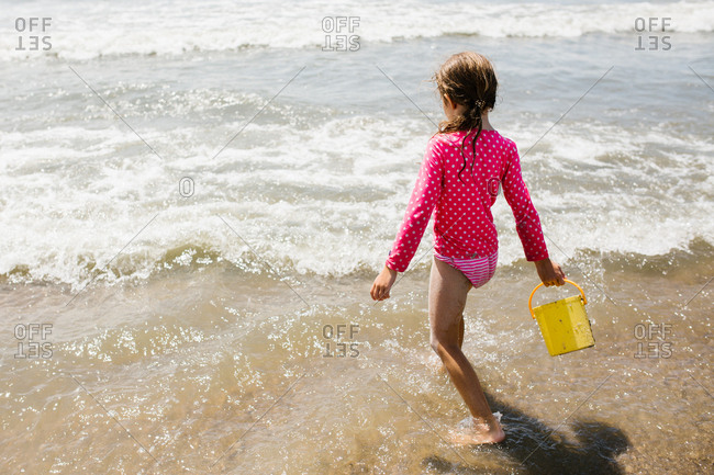 Girl wading in ocean waves carrying a bucket