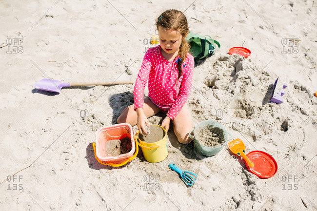 Girl filling buckets with sand at the beach