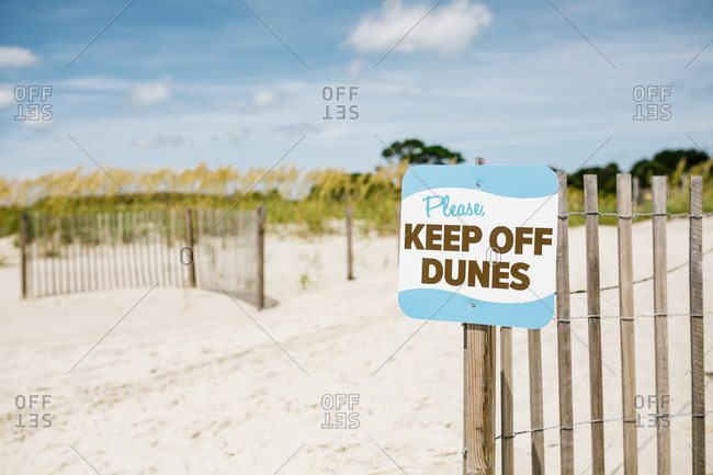 Sign posted at entrance to sand dunes at the beach