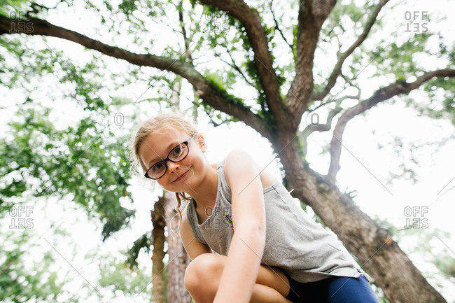 Smiling girl with blond hair wearing glasses outside