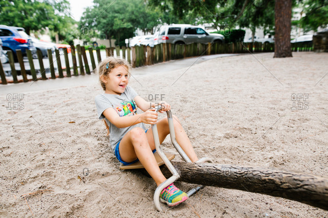 Smiling girl sitting on a seesaw