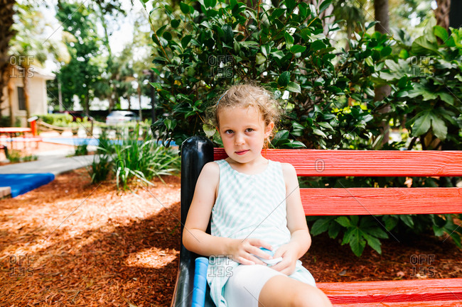 Girl with blond curly hair sitting on a red bench in a public park