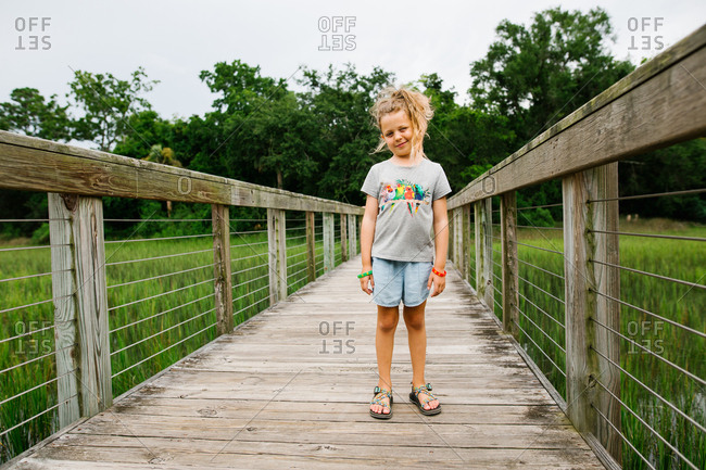 Girl standing on wooden boardwalk over wetlands while taking a nature walk
