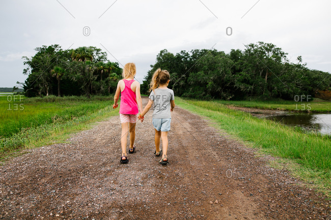 Sisters holding hands walking together on gravel road through natural area
