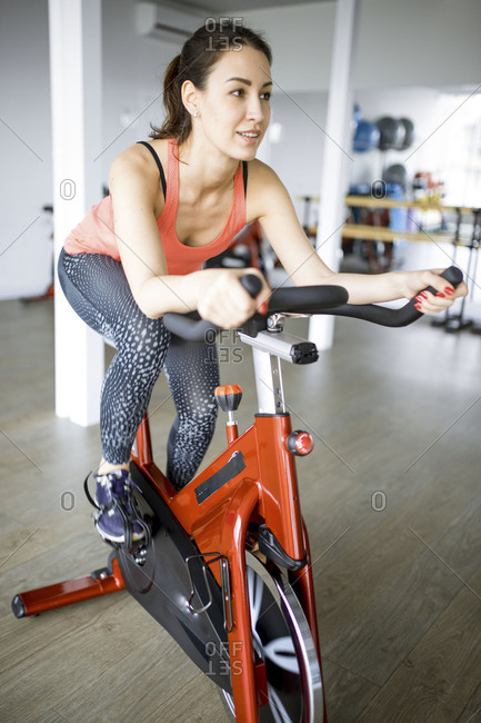 Young woman spinning on a bicycle in a gym