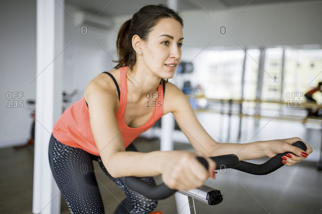 Young woman spinning on a bike in a gym