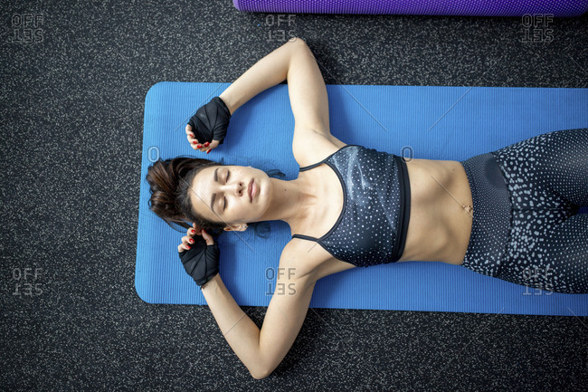 Overhead view of woman laying on yoga mat