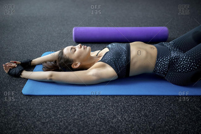 Side view of woman laying on yoga mat