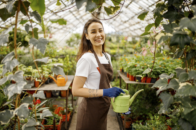 Smiling woman in a greenhouse holding watering can