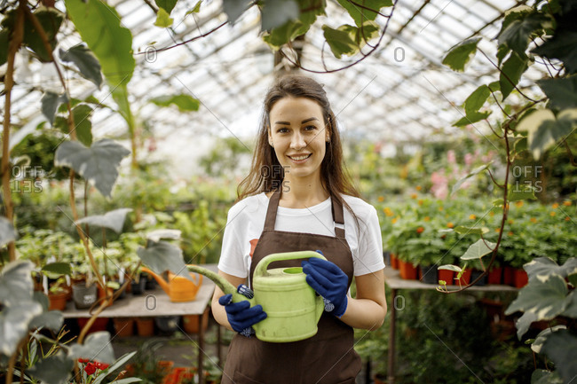 Young woman in a greenhouse holding watering can
