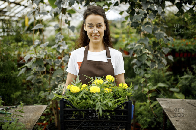 Young woman holding yellow flowers inside a greenhouse