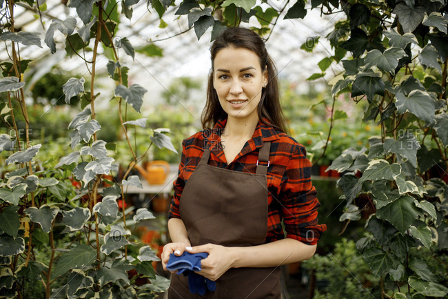 Young woman in plaid shirt standing in a greenhouse
