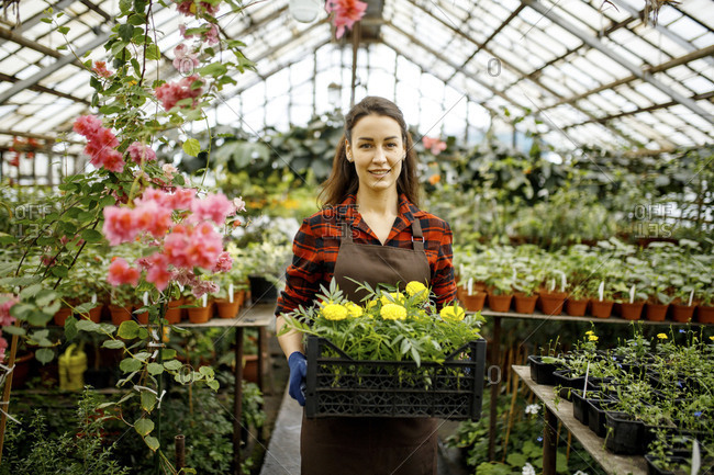 Woman holding yellow flowers in a greenhouse