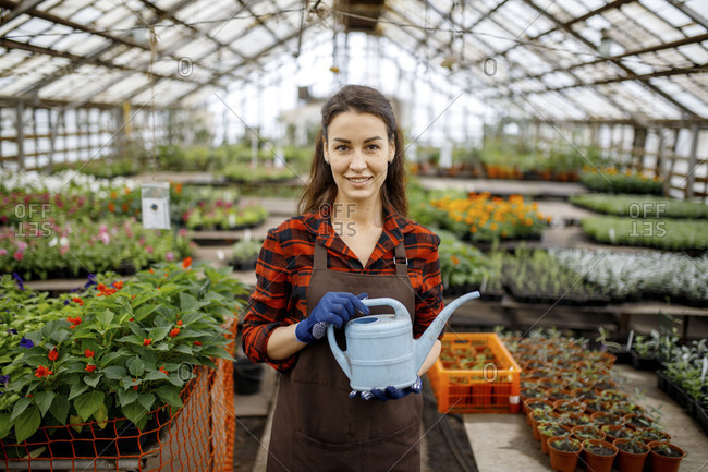 Woman standing wearing apron in a greenhouse