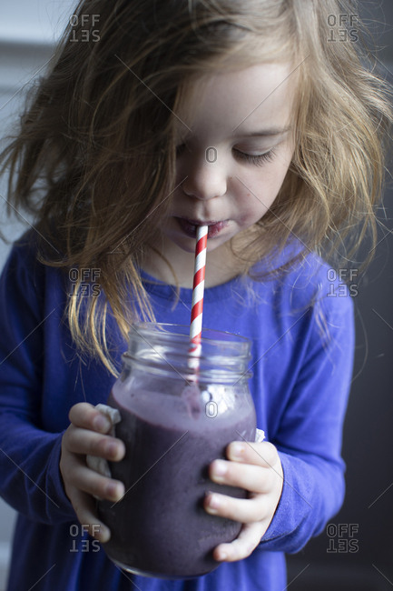 Little girl drinking a smoothie with a straw