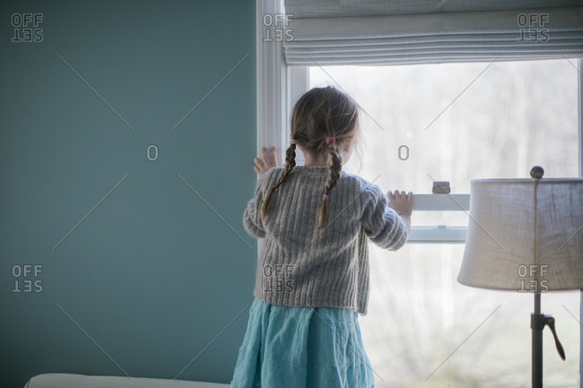 Rear view of a little girl looking out window