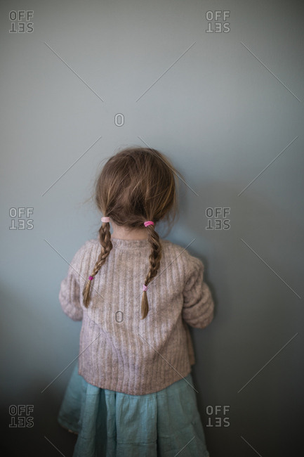 Portrait of a little girl facing a wall