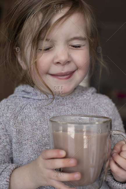 Little girl sipping a cup of hot chocolate