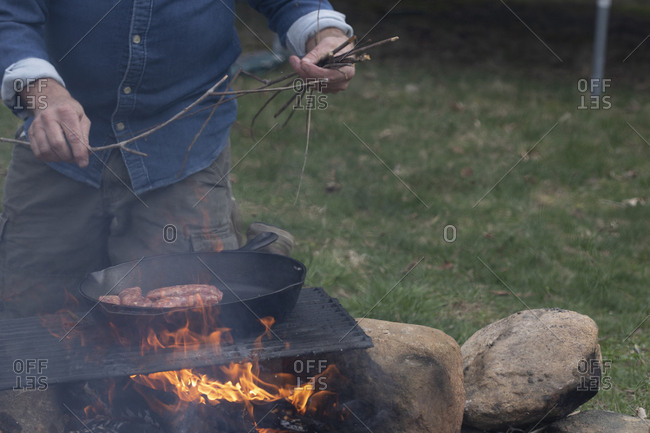 Man grilling sausage on a campfire grill