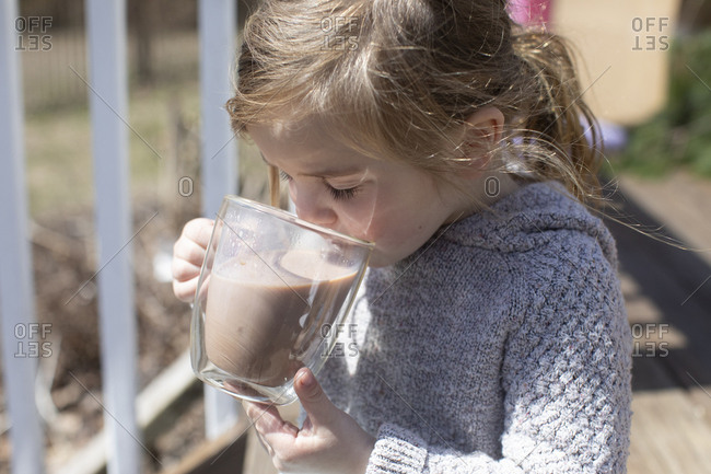 Little girl sipping a cup of hot chocolate outdoors