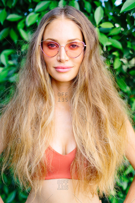 A long haired woman outdoors in an orange swimsuit and matching sunglasses