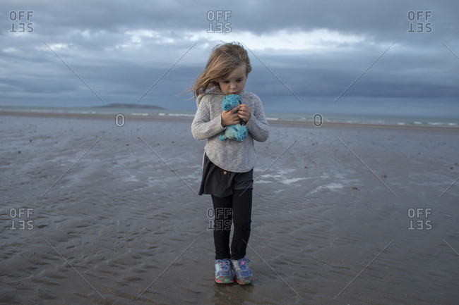 Young girl standing on a beach holding stuffed doll