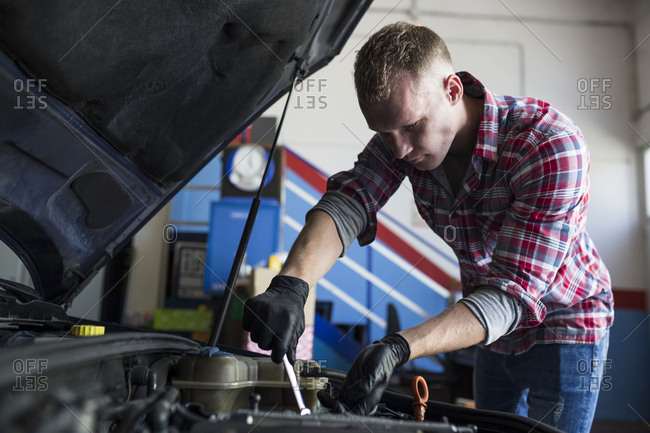 Repairman in black gloves fixing car engine with wrench in Madrid, Spain