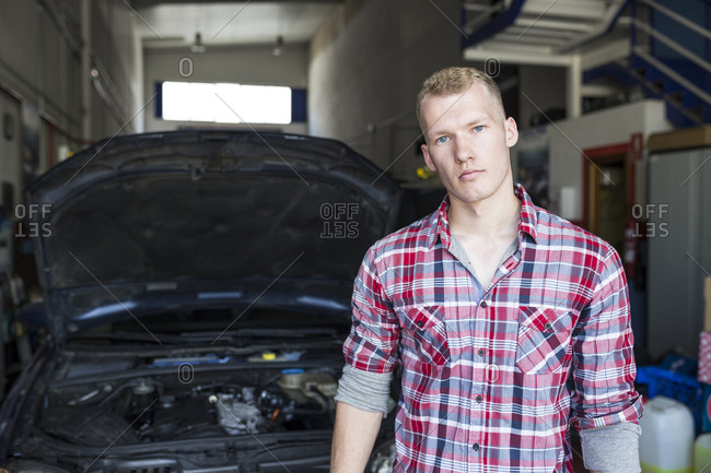 Man in plaid shirt standing near car with opened hood in repair shop