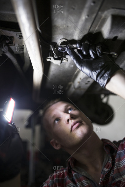 Repairman standing under car fixing it with light and wrench