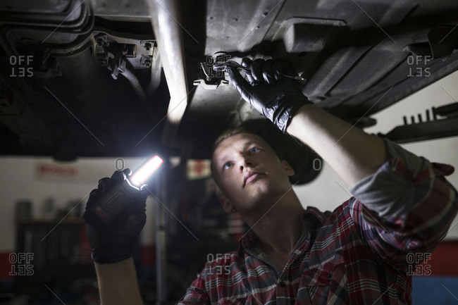 Repairman standing under car fixing it with light and tool