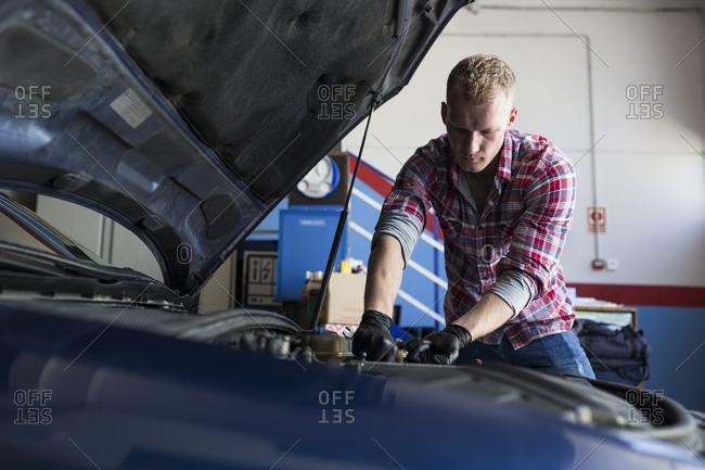 Repairman in black gloves fixing car engine in a shop, Madrid, Spain