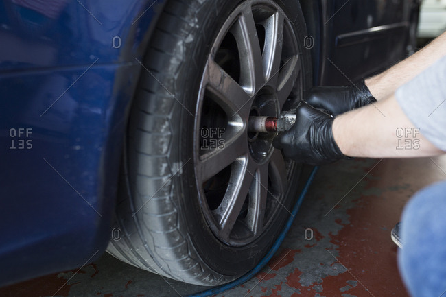 Hands of man tightening lug nuts on car wheel with electric screwdriver