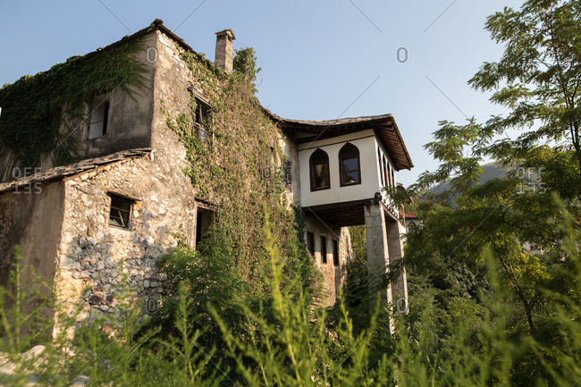 Old stone building surrounded by green plants in Mostar, Bosnia and Herzegovina