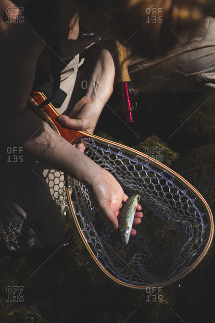 Woman holds trout she has just caught