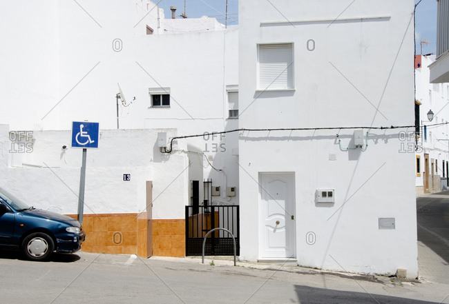 Handicap sign on street in front of white building