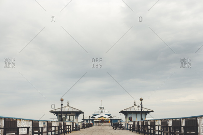 View of Llandudno Pier and carousel on a cloudy day, Llandudno, North Wales, UK